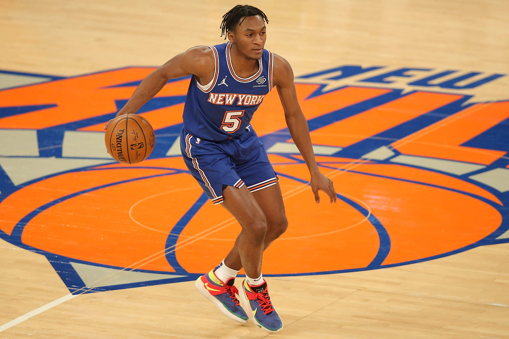 New York Knicks rookie point guard Immanuel Quickley dribbles the ball up the court on offense during an NBA basketball game.