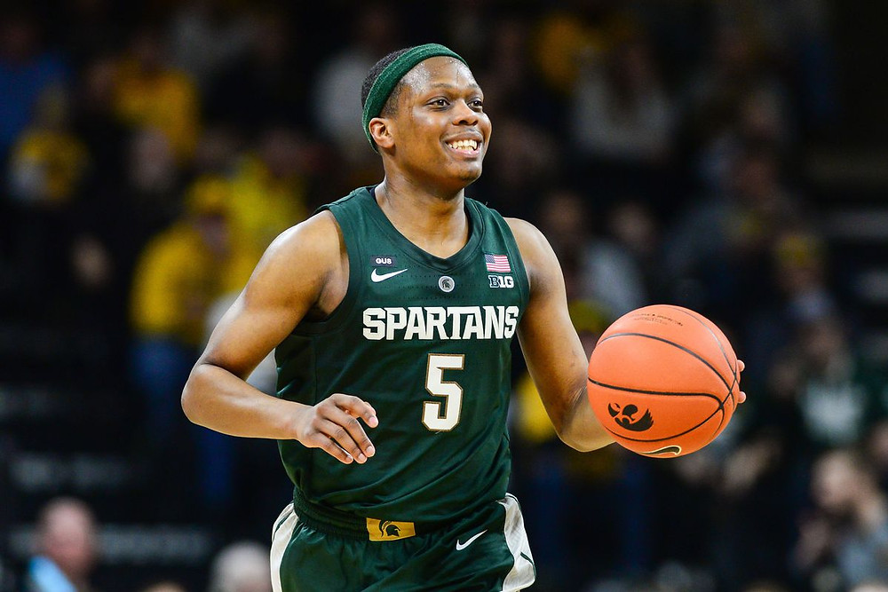 Cassius Winston of Michigan State University smiles as he dribbles the basketball up the court in an NCAA game.