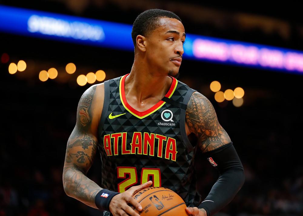 Atlanta Hawks power forward John Collins collects a rebound during an NBA basketball game.