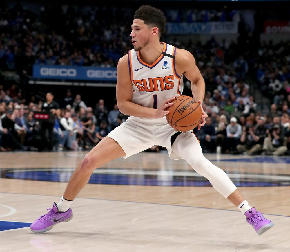 Phoenix Suns shooting guard Devin Booker steps back for a jumpshot in an NBA basketball game.