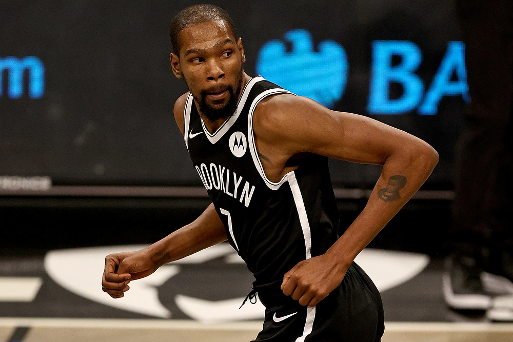 Brooklyn Nets forward Kevin Durant runs back on defense after a successful possession during an NBA basketball game.