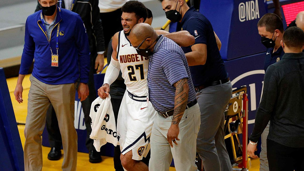 Denver Nuggets guard Jamal Murray hobbles off the court with a torn ACL during an NBA basketball game against the Golden State Warriors on April 12.