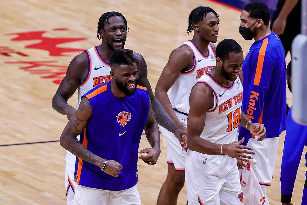 New York Knicks players Julius Randle, Reggie Bullock, Immanuel Quickley, Alec Burks, and Obi Toppin celebrate after a called timeout during an NBA basketball game against the New Orleans Pelicans at Smoothie King Center in New Orleans, Louisiana.
