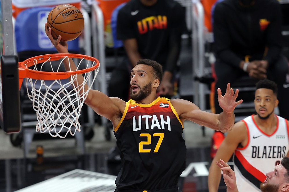 Utah Jazz center Rudy Gobert lays up the basketball during an NBA basketball game against the Portland Trail Blazers.