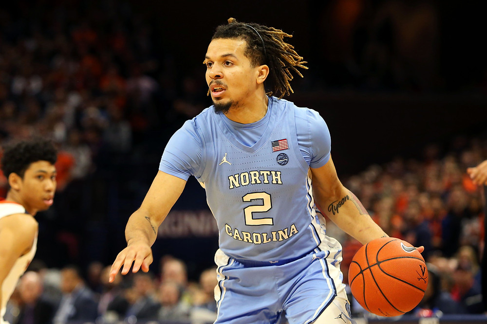 North Carolina point guard Cole Anthony dribbles the ball past Virginia point guard Kihei Clark in an NCAA basketball game.