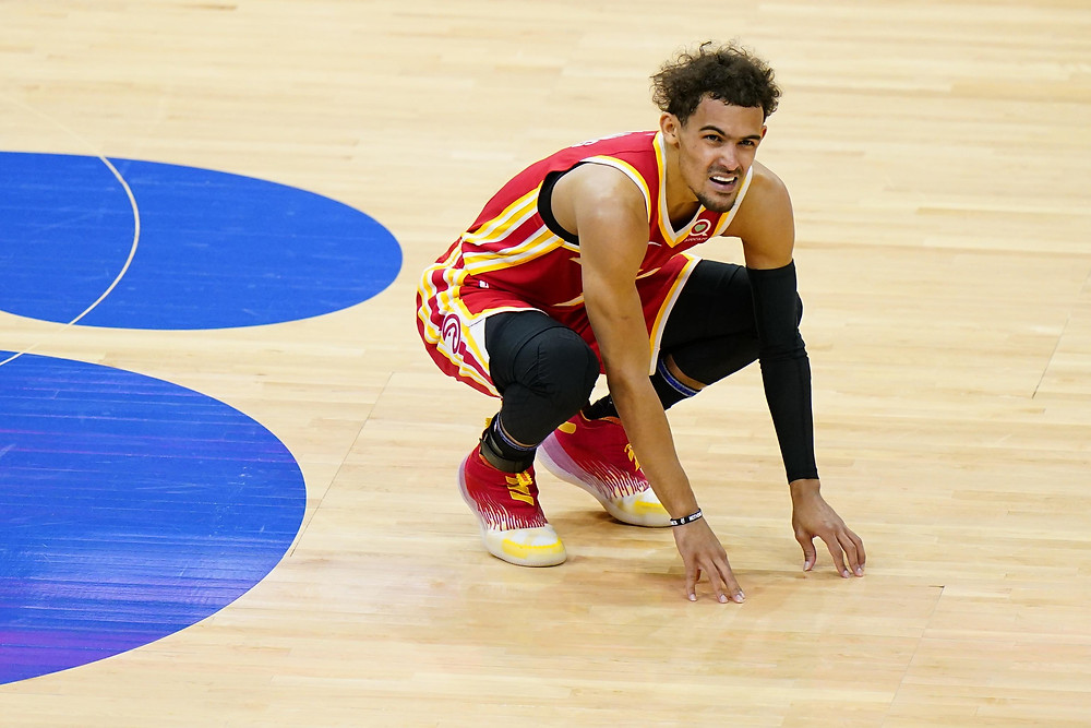 Atlanta Hawks point guard Trae Young crouches after suffering a sprained ankle and bone bruise in his right foot during Game 3 of the Eastern Conference Finals against the Milwaukee Bucks.
