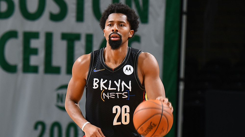 Brooklyn Nets point guard Spencer Dinwiddie dribbles the ball up the court on offense against the Boston Celtics during an NBA basketball game.