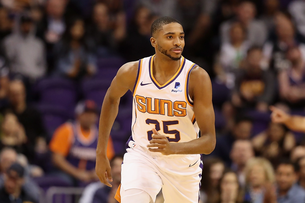 Phoenix Suns small forward Mikal Bridges runs up the court after a made basket during an NBA basketball game.