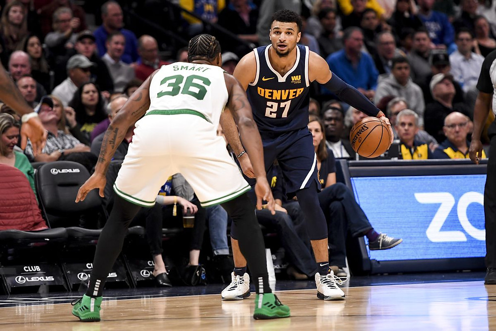 Marcus Smart of the Boston Celtics guards Jamal Murray of the Denver Nuggets in an NBA game.