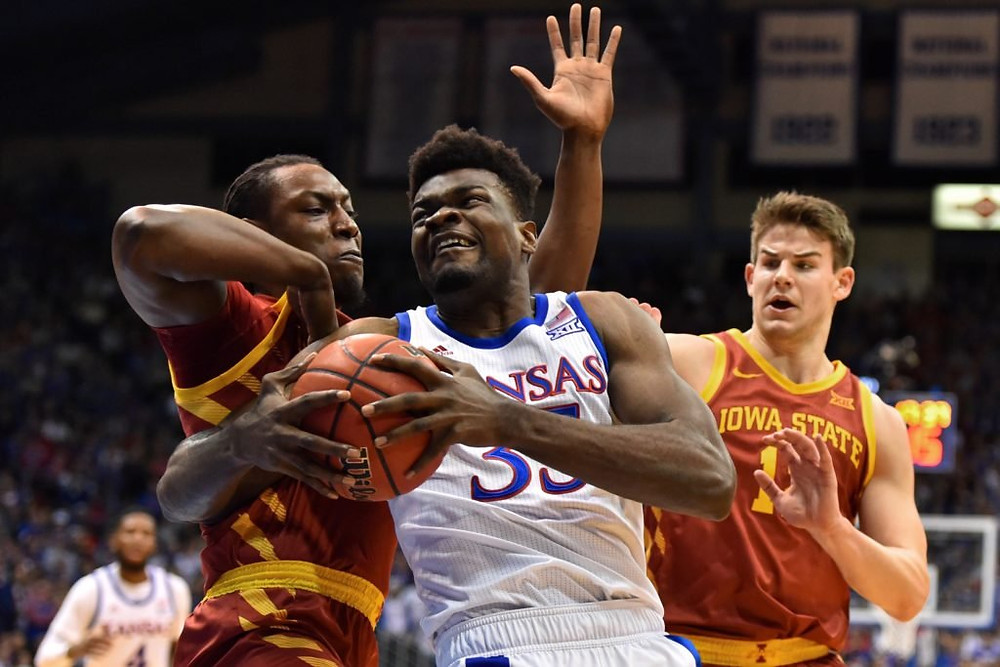 Kansas Jayhawks center Udoka Azubuike fights through two defenders in an NCAA basketball game against the Iowa State Cyclones.