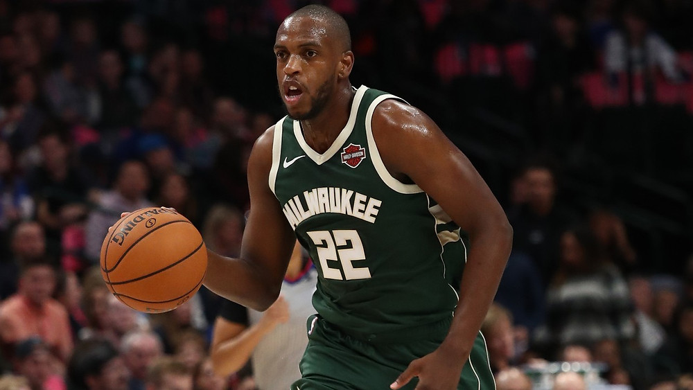 Khris Middleton of the Milwaukee Bucks dribbles the ball up the court in an NBA game.