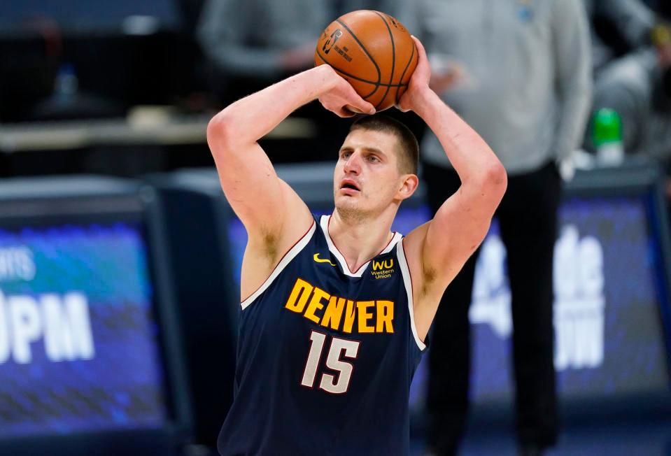 Denver Nuggets center Nikola Jokić attempts a shot during an NBA basketball game.