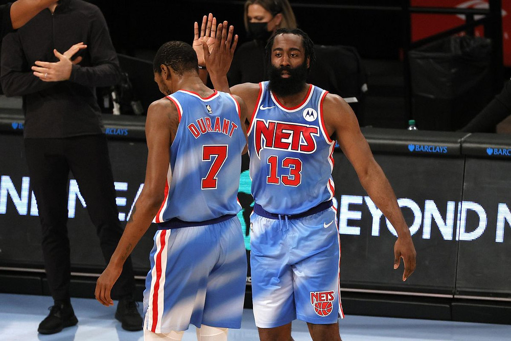 Brooklyn Nets Kevin Durant and James Harden high five during an NBA basketball game at Barclays Center in Brooklyn, New York.