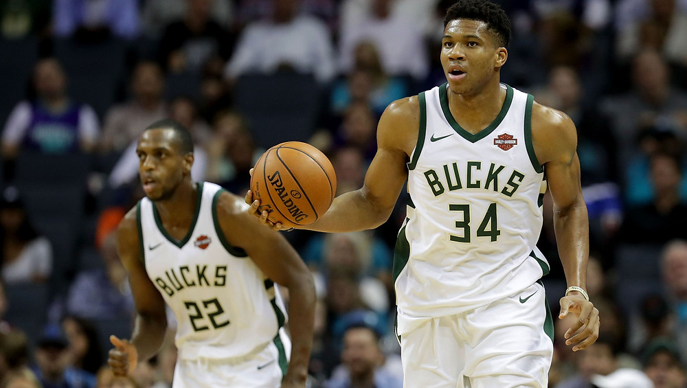 Giannis Antetokounmpo of the Milwaukee Bucks, flanked by small forward Khris Middleton, dribbles the ball up the court on offense during an NBA basketball game.