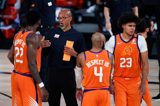Phoenix Suns center Deandre Ayton, point guard Jevon Carter, and small forward Cameron Johnson talk with head coach Monty Williams in an NBA game.