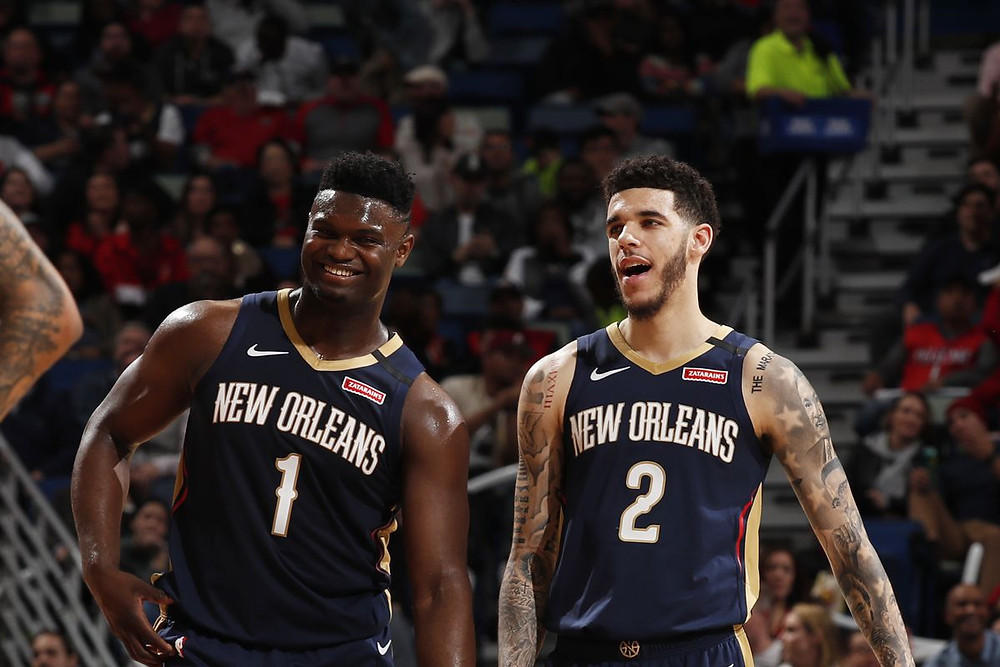 Zion Williamson and Lonzo Ball of the New Orleans Pelicans smile during an NBA game.