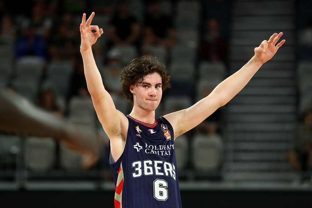 Adelaide 36ers guard Josh Giddey raises his hands in celebration during an NBL basketball game.