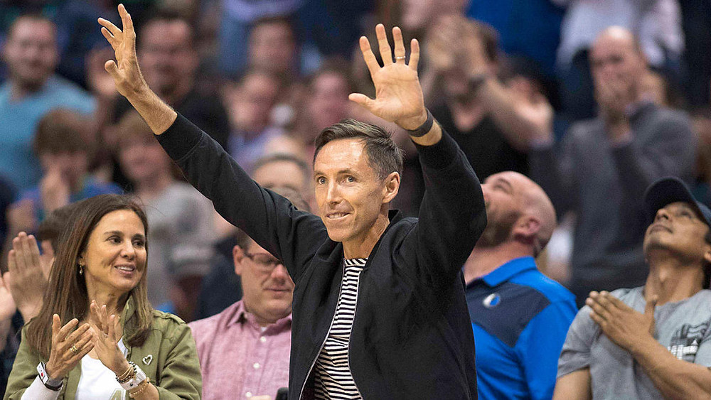 Newly hired Brooklyn Nets head coach Steve Nash acknowledges a cheering crowd during an NBA basketball game.