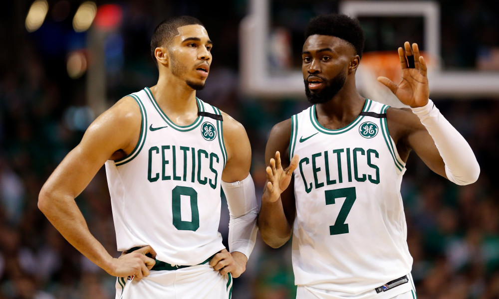 Boston Celtics players Jayson Tatum and Jaylen Brown discuss during a break in the action in an NBA basketball game.
