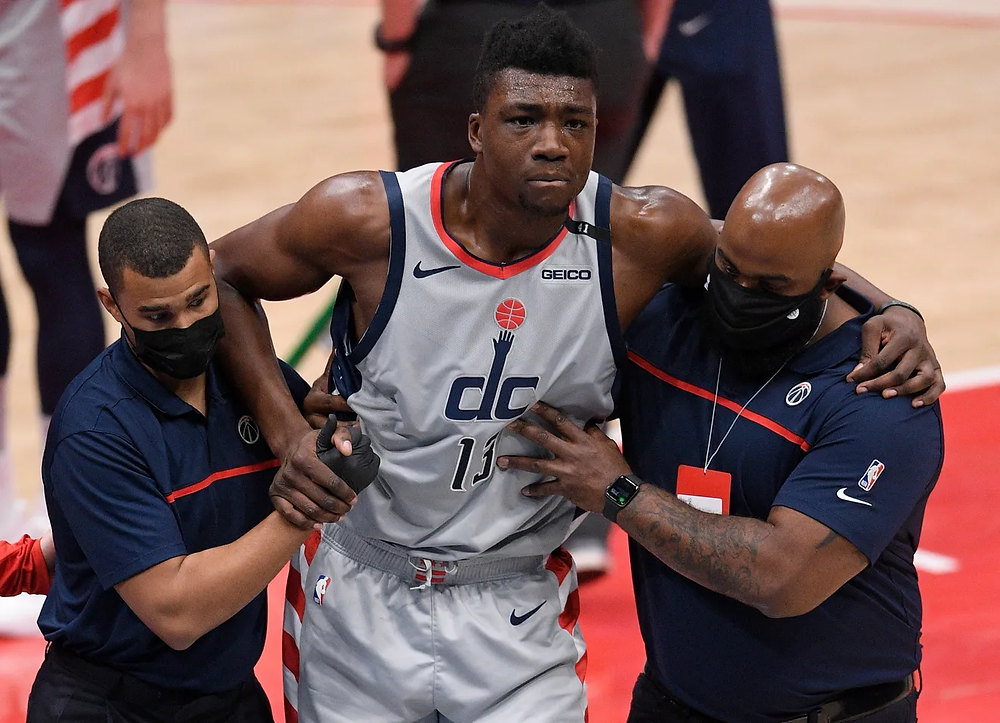Washington Wizards center Thomas Bryant is helped off the court after partially tearing his ACL during an NBA basketball game.