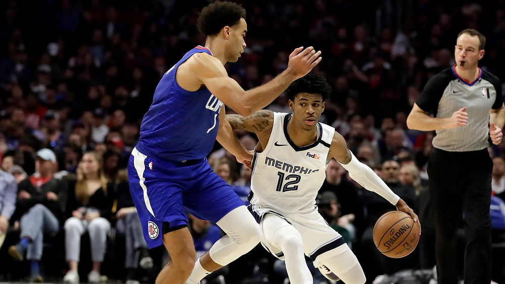 Memphis Grizzlies point guard Ja Morant crosses over Los Angeles Clippers guard Jerome Robinson during an NBA basketball game.