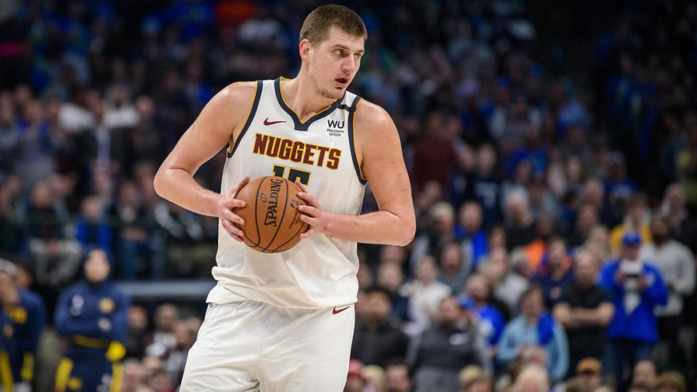 Denver Nuggets center Nikola Jokić prepares to post up with the basketball in his hands during an NBA basketball game.