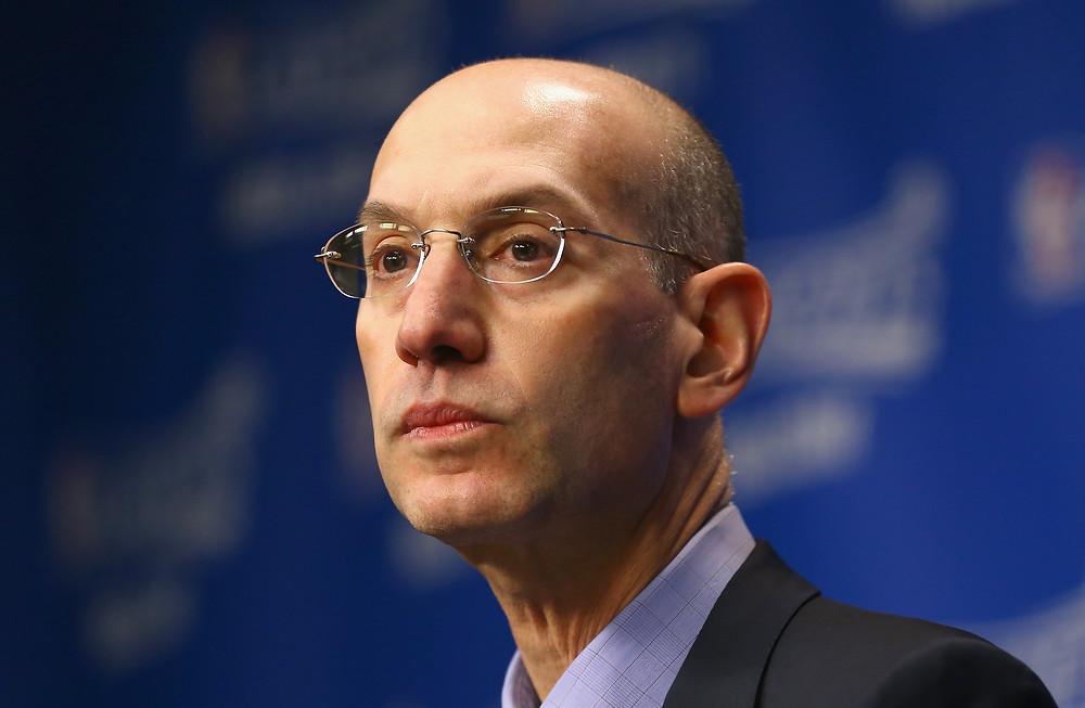 NBA commissioner Adam Silver looks toward a reporter in a press conference.