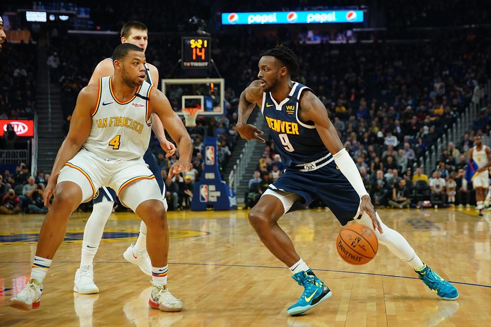 Denver Nuggets forward Jerami Grant drives the basketball against Golden State Warriors forward Omari Spellman in an NBA basketball game.