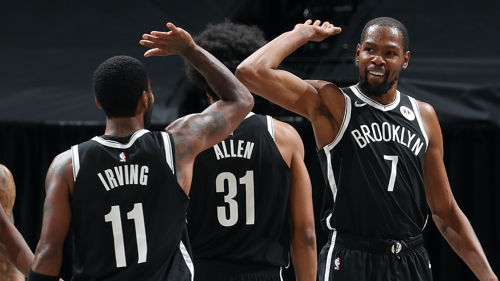 Brooklyn Nets stars Kyrie Irving and Kevin Durant celebrate following a made basket with center Jarrett Allen in the background during an NBA basketball game.