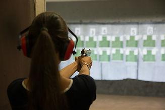 woman-aiming-gun-in-shooting-range-66NLQ