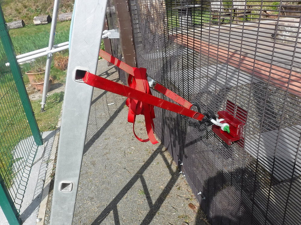 A silver ladder is attached to a 358 security mesh fence using a red QAB Systems bracket