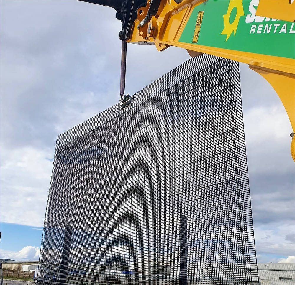 A yellow and green crane lifts a large double 358 mesh fence over an industrial area, utilising the QAB System lifting bracket.