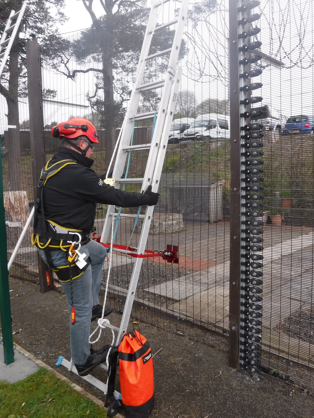 A silver ladder is attached to a 358 security mesh fence using a red QAB Systems bracket as a man in rope access gear climbs the ladder
