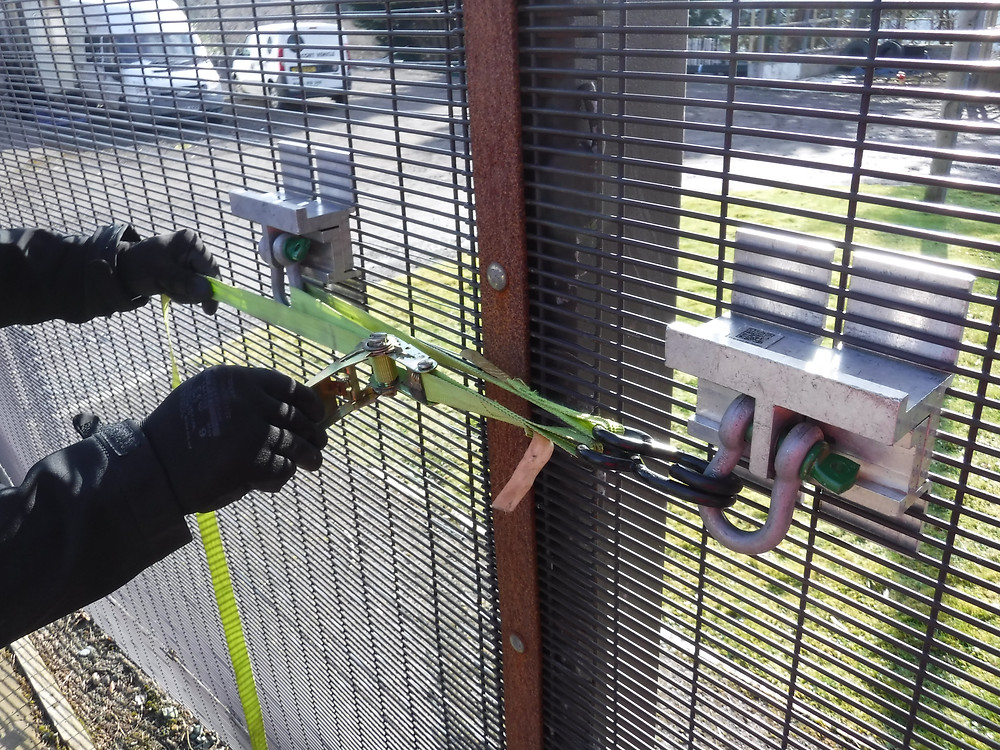 A pair of gloved hands pull a yellow strap between two QAB fence brackets secured to 358 mesh fence line, bringing the panels together.