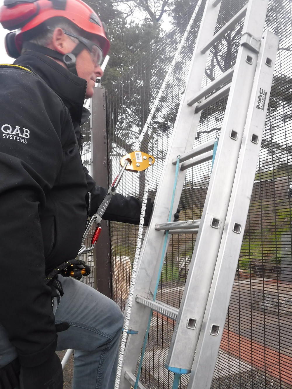 A man climbs a ladder while attached with a rope access fall restraint harness