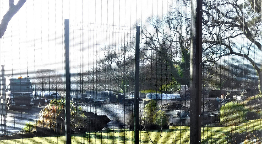 358 security mesh fence surrounding a building yard with lorries and building materials on a sunny day.