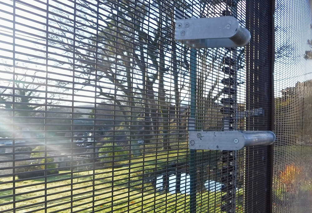 Two metal QAB System fencing brackets are affixed to different points on a 358 Security Mesh fence, overlooking green fields and trees on a sunny day.