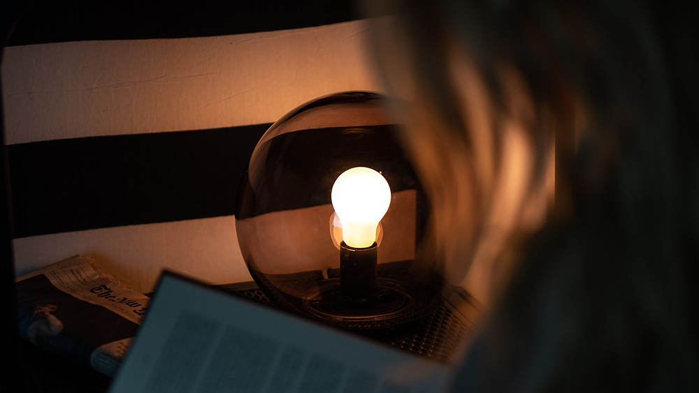 Woman reading with Bedtime Bulb NZ