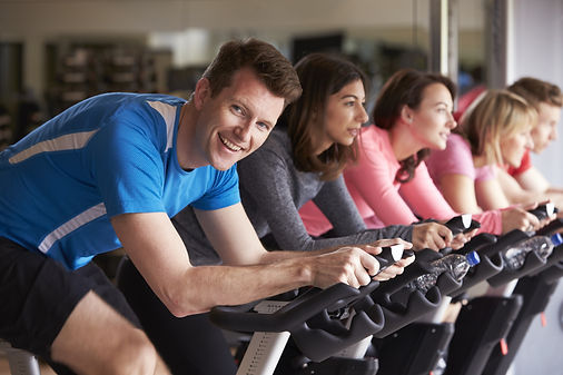 Man in a spinning class at a gym turning