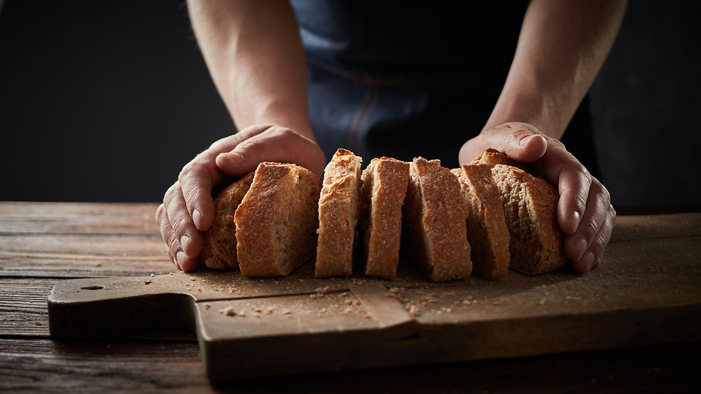 chef-holding-a-bread-in-front-of-a-woode