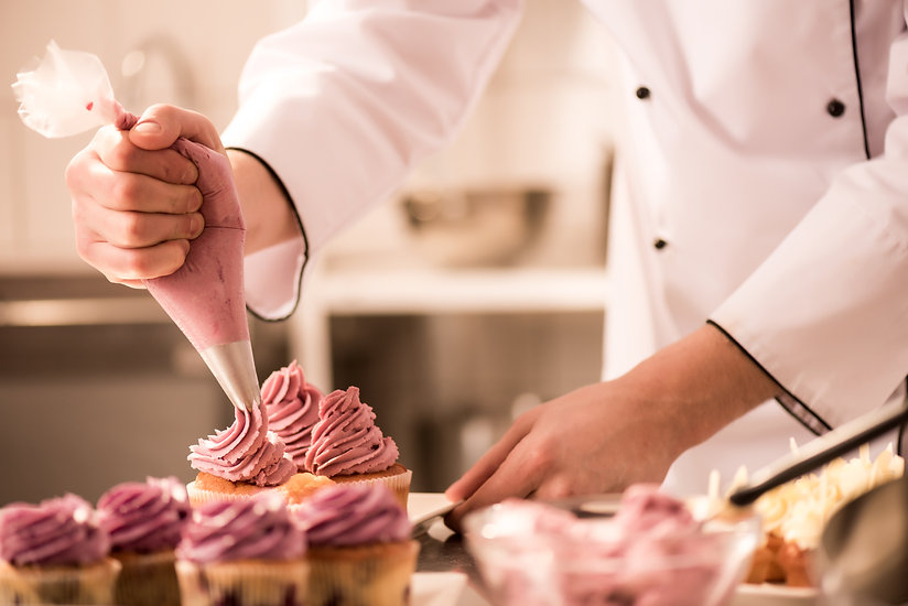 cropped-shot-of-confectioner-putting-cre