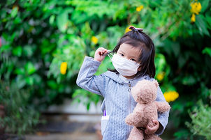 Asian little girl is carrying a teddy bear trying to remove the medical face mask from her