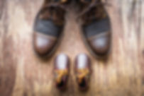 Father and son brown shoes on wooden bac