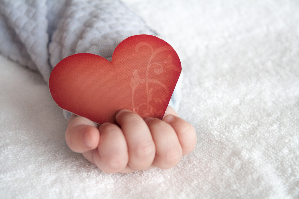 Babies hand holding a heart on soft white blanket