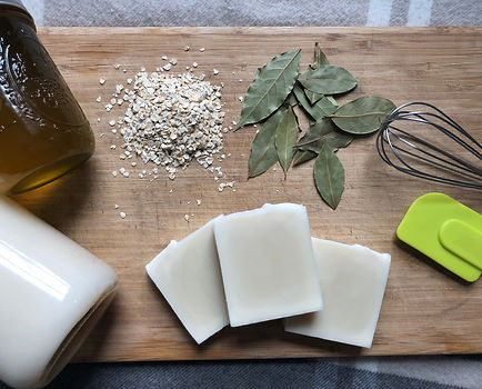 A sampling of natural, local ingredients on a wood board with our back to basics lard and olive oil soap bar