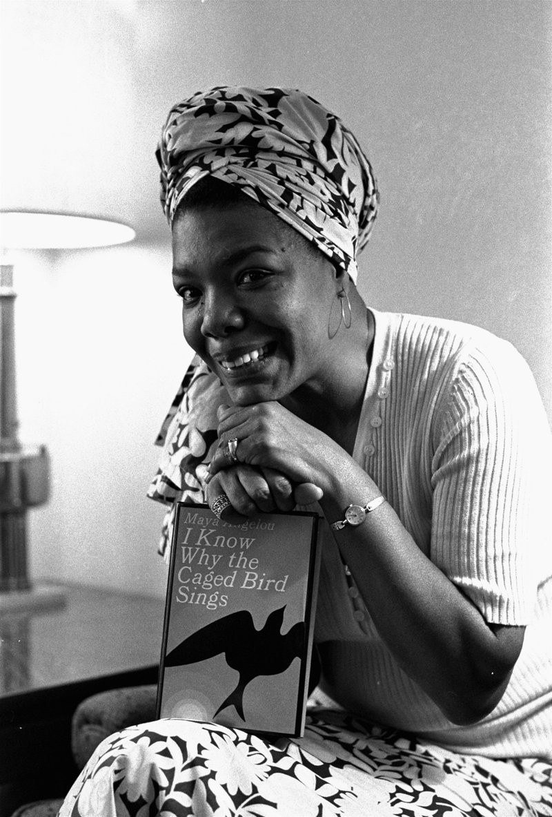 Maya Angelou smiling and showing her book. Her hands are prompted up on top and she has her chin on top of her hands.