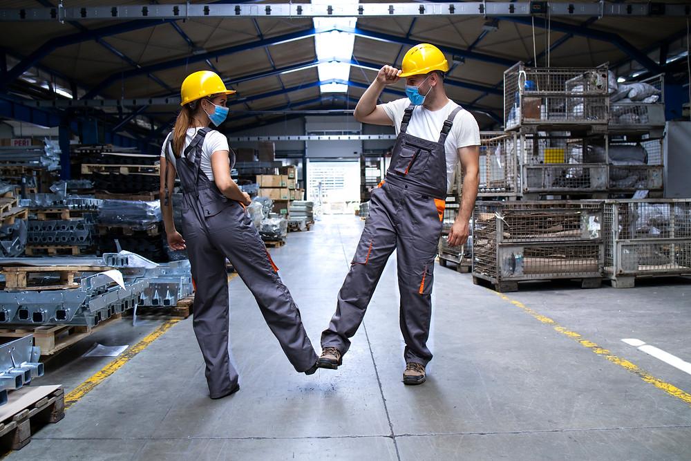 Dois trabalhadores com máscaras e uniformes durante a pandemia