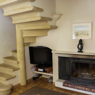 Striking circular stone staircase and Provençal fireplace in your Provence escape, La Jassine