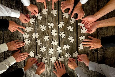 businessmen-hands-holding-puzzle-pieces-