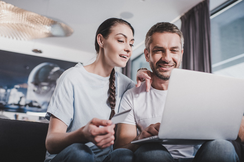 smiling-couple-with-laptop-doing-online-shopping-b-DLUGTAG.jpg